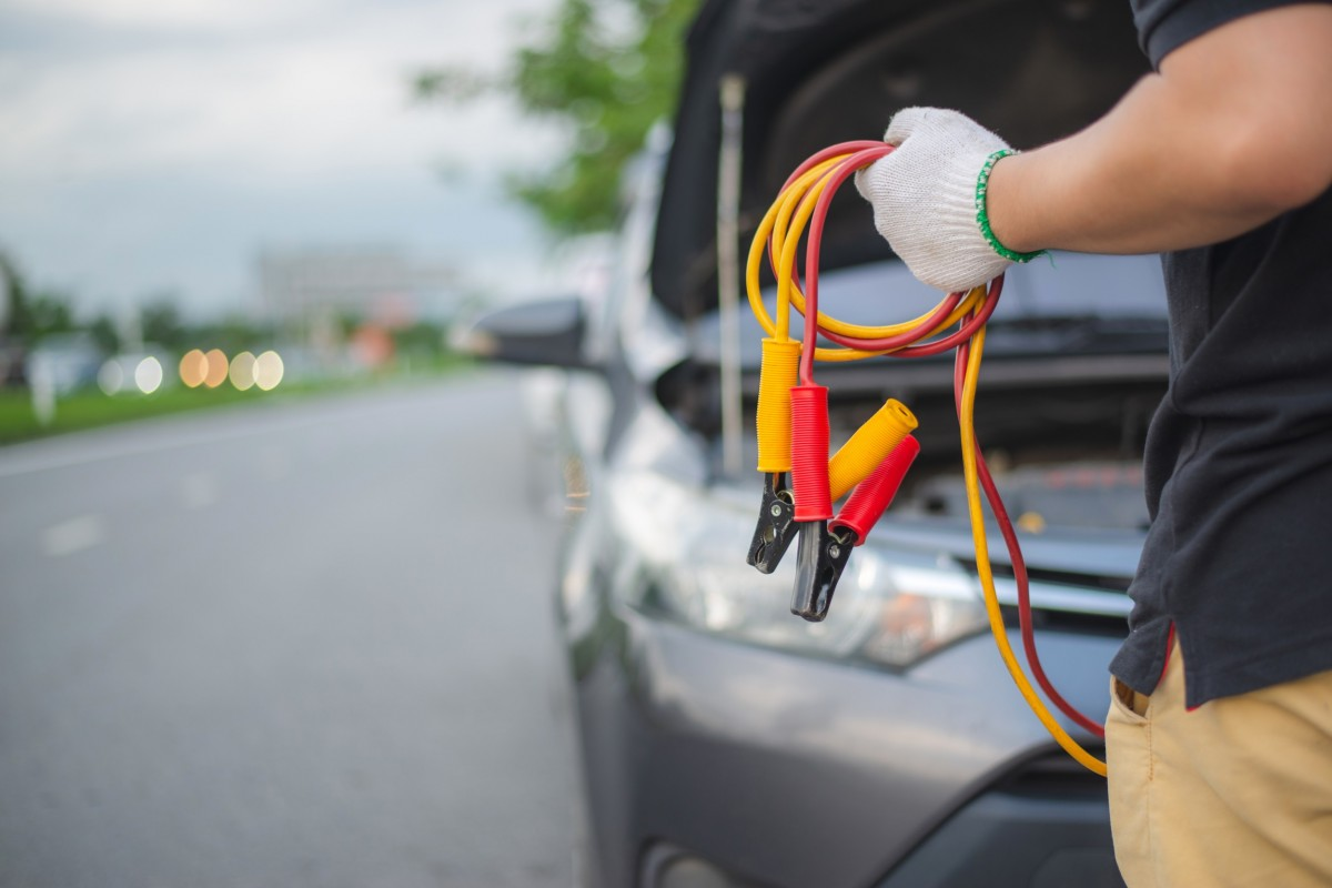 jumper cables being held by person in front of car